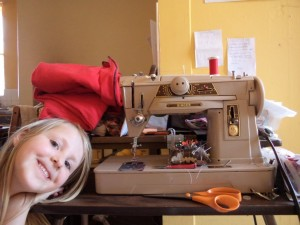 small girl standing to one side of sewing machine