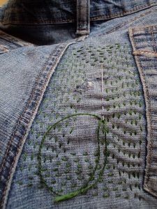 Visible mending green reinforcing stitching